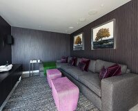 Small pink ottomans and grey sofa in elegant modern interior with striped grey and brown wallpaper