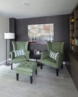 Green armchairs and footstool next to bookcase in comfortable seating area