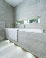 Fitted bathtub with grey-tiled front and wall and narrow, illuminated niche shelf with mirrored back wall