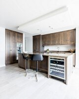 Black bar stools at free-standing counter with integrated wine cooler in designer kitchen with wooden cupboard doors