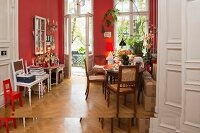 Vintage furnishings in period living room with red walls and herringbone parquet floor