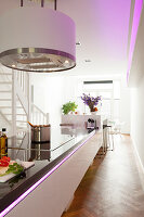 Modern island counter with integrated induction hob below cylindrical extractor hood lit by pale purple LED lights