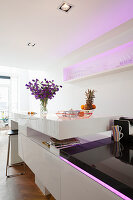 Island counter with white, polished surface and integrated, pale purple LED lighting in open-plan kitchen