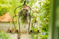 Suspended candle chandelier decorated with herb bouquet