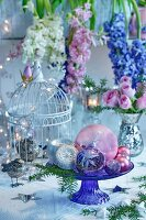 Baubles on glass cake stand in front of flower arrangement of hyacinths and roses in mercury silver vase