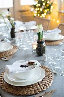 Christmas table festively set with raffia place mats, white crockery and hyacinths