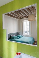 View into simple bedroom with rustic wood-beamed ceiling through opening in green-tiled wall