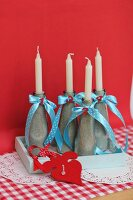 Candle holders made from bottles filled with sand and decorated with ribbons & decorative numbers