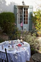 Set breakfast table in autumnal garden outside old country house with French windows