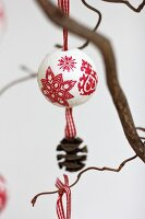 Polystyrene bauble festively decorated using napkin decoupage and with ribbon and pine cone