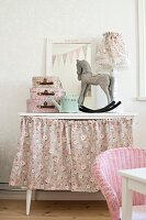 Rocking horse ornament and small cases on dressing table with floral skirt