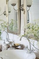 Two silver-framed mirrors above twin sinks with vintage-style tap fittings