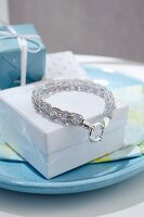 A beaded bracelet with a knitted encasing on a white box