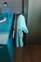 A turquoise towel on a stainless steel towel rail next to a washstand in a modern bathroom