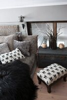 Upholstered footstool and trunk next to comfortable couch