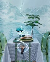 Dining table with green plexiglas chairs in front of wall with mountain landscape & fairy lights