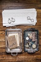 Pocket watches, vintage-style spectacles and stacked lace doilies on antique trays