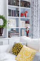Red Advent horse figurine and nutcracker in white shelving compartments behind white sofa with yellow and grey scatter cushions