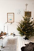 Decorated Christmas tree on white wooden floor, toys on table in front of retro standard lamps