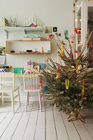 Decorated Christmas tree next to desk and wooden chair below wall-mounted shelves