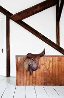Saddle on wooden balustrade below wooden beams