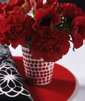 Red carnations in red and white spotted vase next to black and white fabric