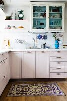White-painted, L-shaped kitchen counter and wall-mounted, country-house-style cabinet