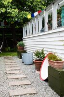 Stepping stones amongst gravel and potted plants against weatherboard greenhouse façade