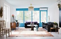 Airy living room with blue window frames and retro furniture