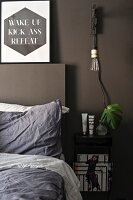 Pendant lamp with bulb above bedside table next to bed against dark, painted wall