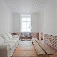 White sofa against wall opposite rustic wooden bench in white living room with tiled dado