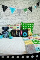 Colourful bedspread and soft toys on bed below bunting against wallpaper with graphical pattern of animals