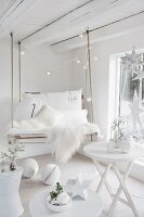 DIY swing made from pallet with white sheepskin rug and cushions in white room with Christmas decorations