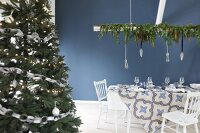 Christmas dining table set in blue and white next to decorated Christmas tree