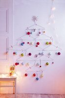 A Christmas tree made of clothes hangers with colourful baubles as wall decoration