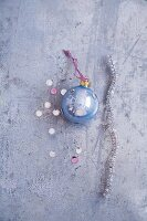 A pipe cleaner, light-blue Christmas bauble and glitter confetti