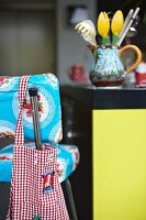 Gingham apron hung on brightly patterned bar stool in front of kitchen utensils on counter