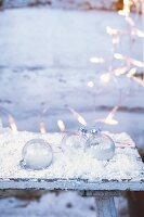 Glass Christmas baubles in snow