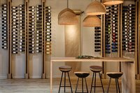 Vintner's shop with minimalist wooden counter, bar stools, cork lampshades and wine bottles in modern shelving system