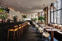 Restaurant with bar and dining tables, sheepskins on classic chairs and Scandinavian designer pendant lamps