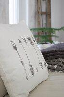 Cushion with arrow motifs printed on white cover