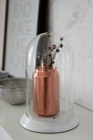 Copper-coloured drinks can used as vase under glass cover