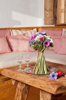 Free-standing bouquet of anemones stood in dish on rustic, solid wooden table
