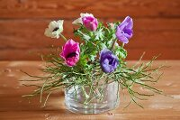 Anemones and bilberry stems in glass bowl