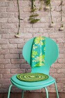 Crocheted seat pad on turquoise chair against brick wall