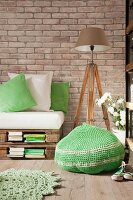 Green crocheted pouffe, pallet sofa and standard lamp on wooden tripod in vintage interior