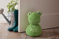 Crocheted frog doorstop on wooden floor