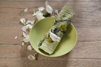 Springlike arrangement of crocheted flowering tendril wrapped around linen napkin on green plate on table