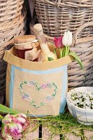 Git bag embroidered with heart motif in front of baskets