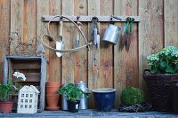 Various gardening utensils, vintage milk churn and plants against board wall